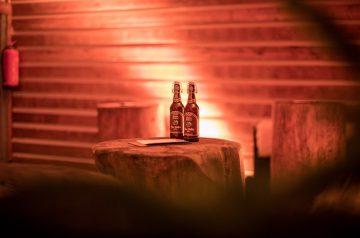 Weihnachtsfeier 2019 Hexenkessel: Auf einem Baumstumpf, der als Stehtisch dient, stehen zwei Bügelflaschen Bier.
